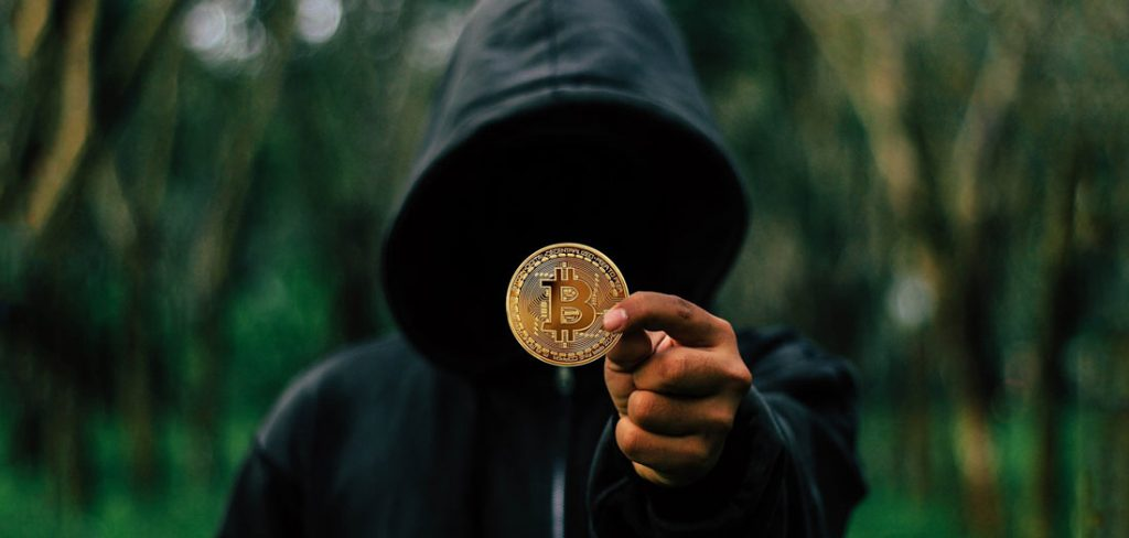 Thief with black hood and bitcoin